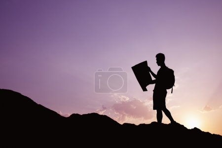 Silhouette of young man looking at a map