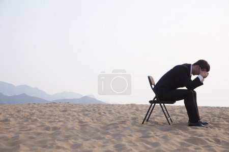 Businessman sitting with his head in his hands
