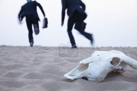 Businessmen running away from an animal skull