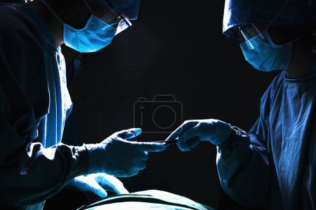 Surgeons working and passing surgical equipment