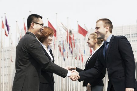 Business people meeting and shaking hands outdoors