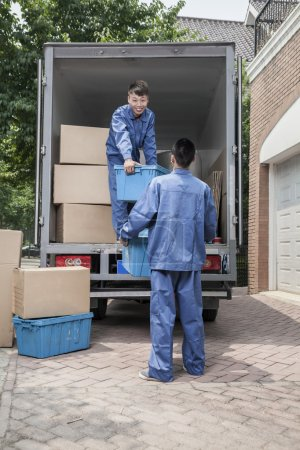 Photo for Movers unloading a moving van, passing a cardboard box - Royalty Free Image