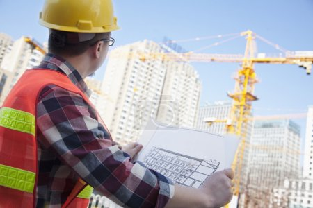 Photo pour Architecte regardant un plan directeur en plein air sur un chantier de construction - image libre de droit