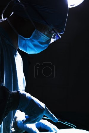 Surgeon holding surgical equipment