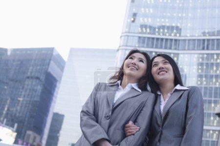 Businesswomen linking arms