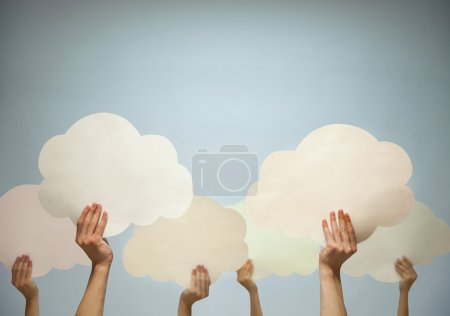 Multiple hands holding cut out paper clouds