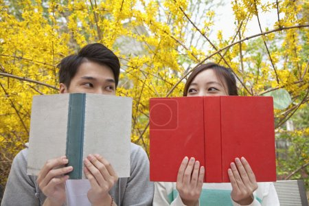 Couple looking at each other over the top of their books