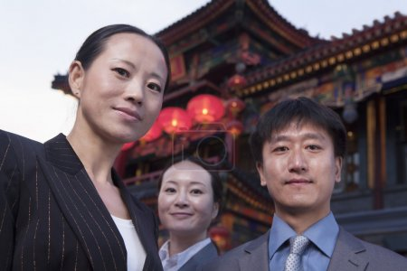Three businesspeople with Chinese architecture