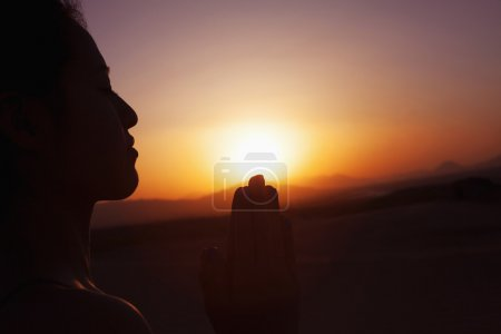 Photo for Serene young woman with hands together in prayer pose in the desert in China, silhouette, sun setting - Royalty Free Image