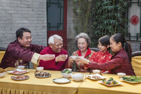 Family with cups raised toasting over a Chinese meal