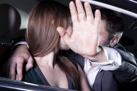 Couple kissing in car at a red carpet event