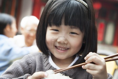 Photo for Portrait of little girl eating rice - Royalty Free Image
