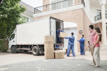 Photo for Young couple watching movers move boxes from the moving van - Royalty Free Image