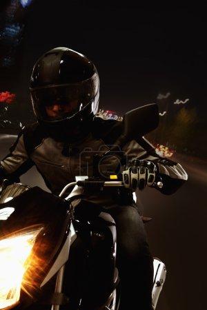 Photo pour Homme conduisant une moto dans la nuit dans les rues de Pékin - image libre de droit
