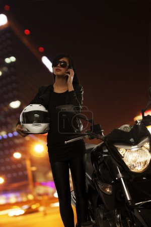 Woman talking on the phone beside her motorcycle