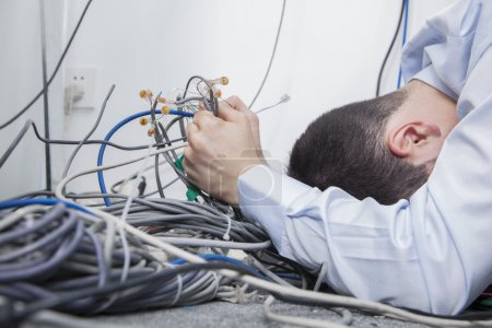 Photo for Frustrated man lying down trying to figure out and sort computer cables - Royalty Free Image