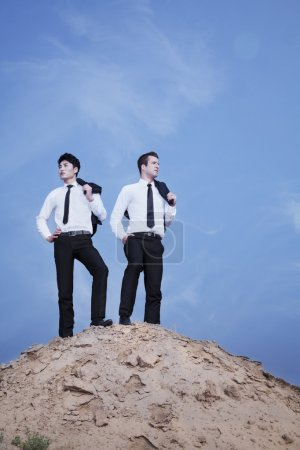 Two young businessmen standing on the top of the hill