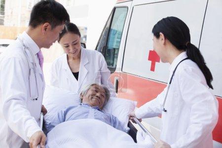 Doctors wheeling in a elderly patient