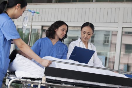 Paramedics and doctor looking down at the medical record of patient