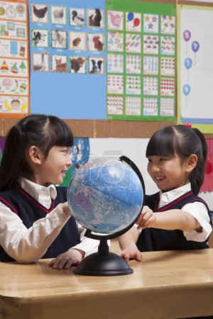 Schoolgirls looking at a globe in the classroo