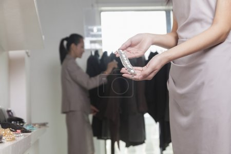 Woman holding piece of jewelry at store