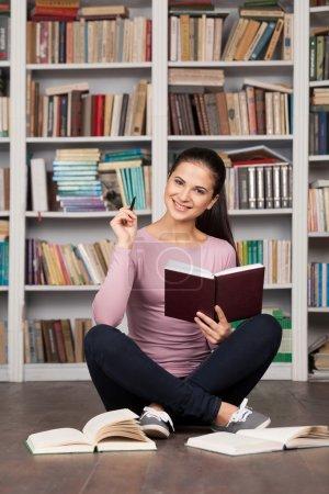 Photo pour Se préparer pour son examen final. belle jeune étudiante tenant livre et souriant tout en étant assis sur le sol à la bibliothèque - image libre de droit