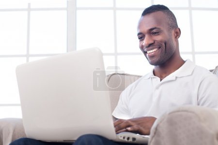 Photo for Working at home. Cheerful African man using computer and smiling while sitting on the chair - Royalty Free Image