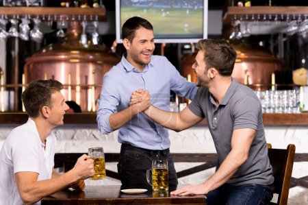 Photo for Old friends meeting. Three cheerful friends meet each other in beer pub - Royalty Free Image