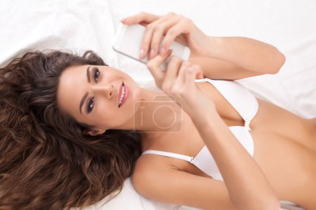 Woman in lingerie holding a mobile phone