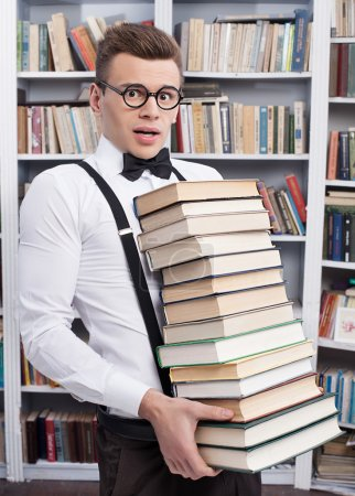 Shocked young man carrying a heavy book stack