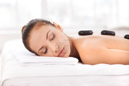 Hot stone therapy. Side view of attractive young woman lying on front and keeping eyes closed with spa stones on her back