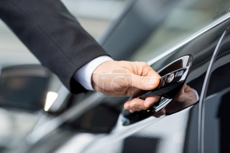 Photo for Opening his new car. Close-up of male hand holding the car handle - Royalty Free Image