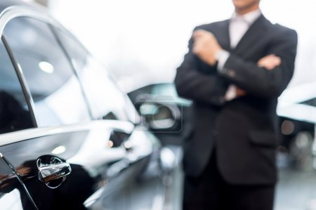 Photo for Choosing a car at dealership. Thoughtful grey hair man in formalwear leaning at the car and looking away - Royalty Free Image