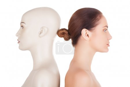 Beautiful young shirtless woman standing her back to the mannequin