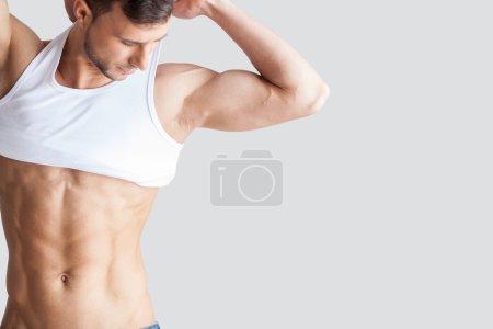 Muscular man taking off tank top