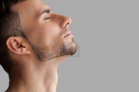 Foto de Hombre guapo barba. vista lateral del hombre guapo joven barba manteniendo los ojos cerrados estando aislados sobre fondo gris - Imagen libre de derechos