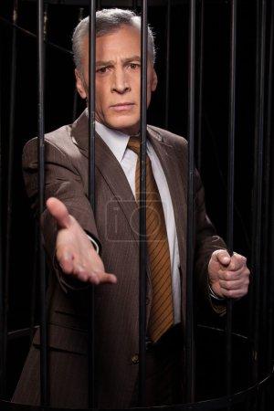Photo pour Crois-moi ! Frustré homme âgé en tenue de cérémonie debout derrière une cellule de prison et étirant la main alors qu'il était isolé sur fond noir - image libre de droit