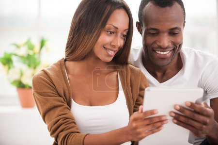 African couple using digital tablet