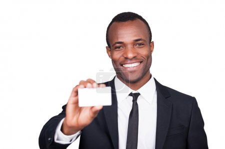 Photo for Here is my business card. Handsome young African man in formalwear showing his business card and smiling while standing isolated on white background - Royalty Free Image