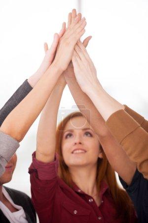 Foto de Unidad de personas. Grupo de jóvenes alegres de pie uno al lado del otro y tomados de la mano - Imagen libre de derechos