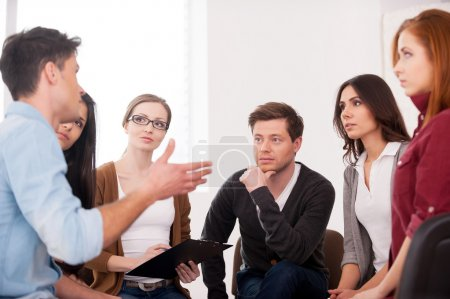 Photo for I want to share my problem. Group of people sitting close to each other while man telling something and gesturing - Royalty Free Image