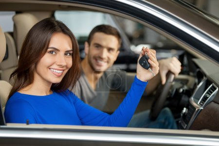 Couple sitting inside of their new car while woman showing keys