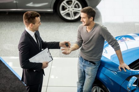 Car salesman making deal with customer at the dealership