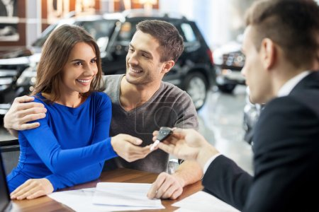 Car salesman giving the key of the new car to the young attractive owners