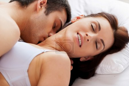 Beautiful young loving couple having sex while lying in bed