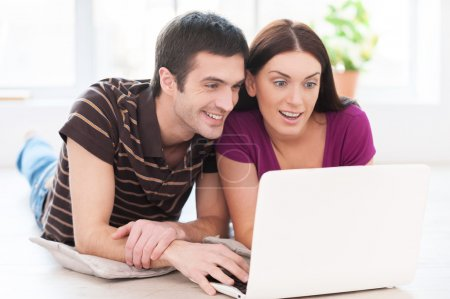 Beautiful young couple working on laptop together while lying on the floor