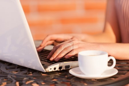 Woman working at laptop while sitting at the outdoor cafe