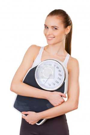 Attractive young woman in sports clothing holding weight scale