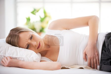 Frustrated young woman holding hands on stomach and looking at camera