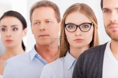 Woman looking at camera while standing in a row with other people